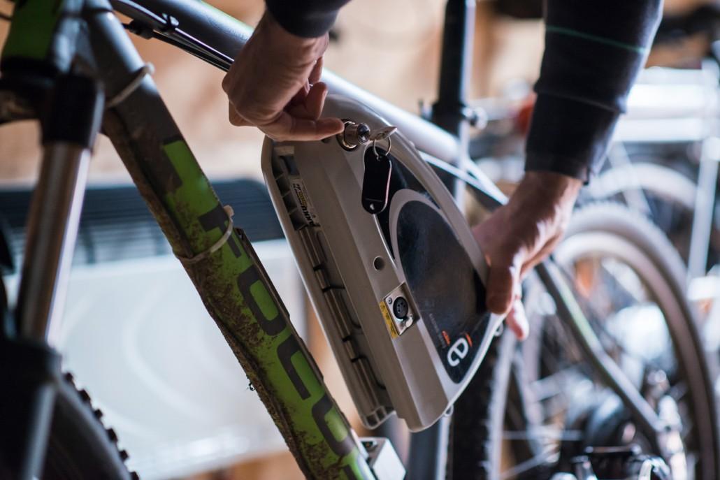 Mitarbeiter entnimmt den Fahrrad Akku vor der Akku Reparatur